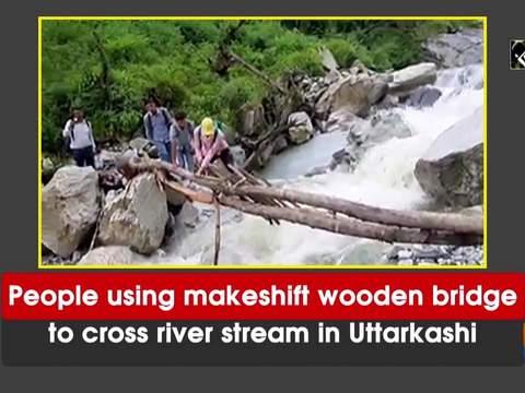 People using makeshift wooden bridge to cross river stream in Uttarkashi