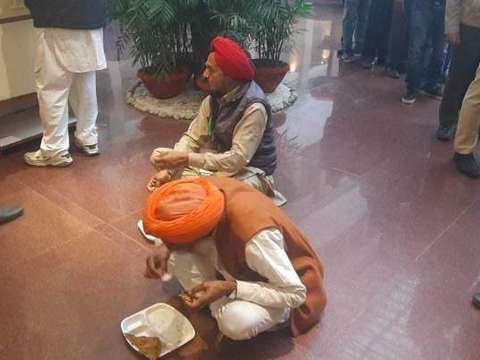 Farmer leaders sit at Vigyan Bhawan floor to have meal during tea break