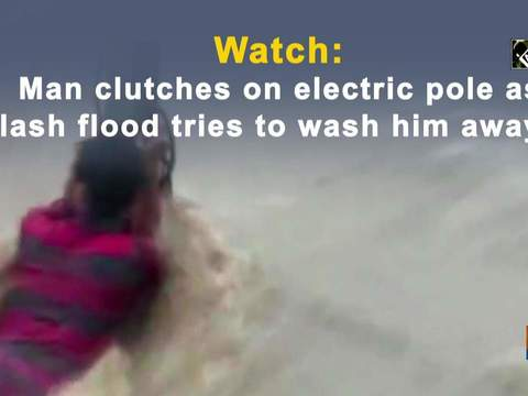 Watch: Man clutches on electric pole as flash flood tries to wash him away
