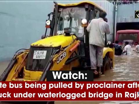 Watch: State bus being pulled by proclainer after it stuck under waterlogged bridge in Rajkot